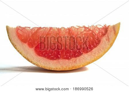 Closeup of a grapefruit wedge on a white background