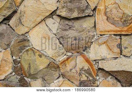 The wall is lined with beige cobblestones of various sizes fastened with concrete.