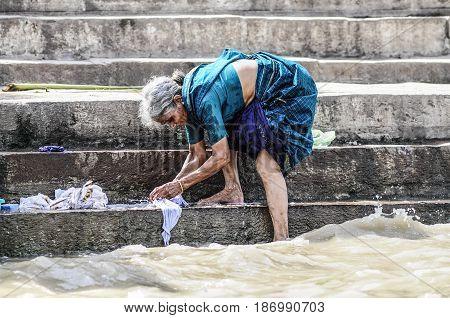 Varanasi India september 19 2010: Old indian woman making laundry in ganges river in Varanasi.
