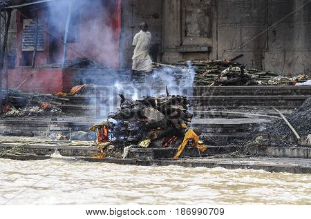 Varanasi India september 2010: Indian cremation funeral in ghat by the ganges river where human body is burning.