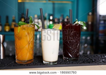 Exotic alcohol party cocktails in restaurant at bar background. Glasses on bar table, refreshing drinks with straws.