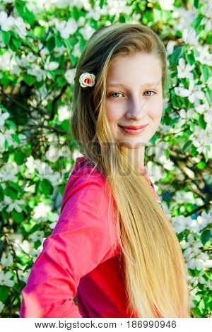 Portrait of a girl against the background of a flowering quince tree