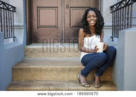 Black woman drinking coffee on front stoop
