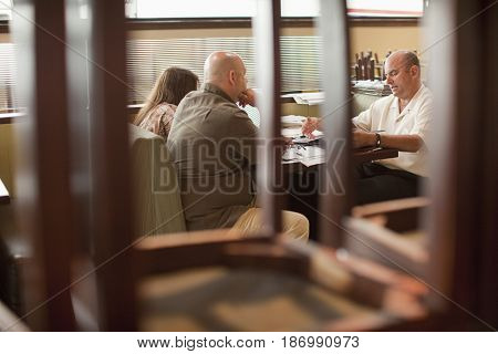 Caucasian restaurant owner working with co-workers in booth