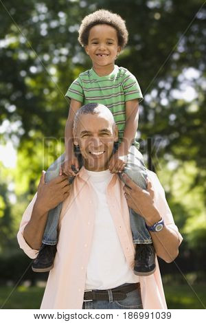 Black father carrying son on shoulders