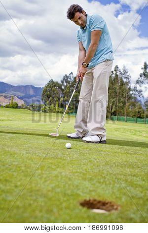 Hispanic man putting golf ball