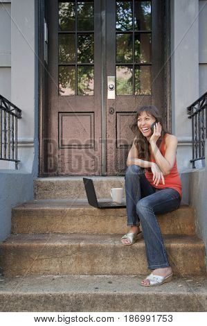 Mixed race woman sitting on front stoop with cell phone and laptop