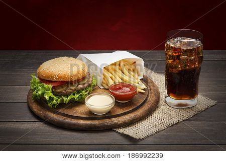 Fast food. Meat burger, potato chips and glass of cola drink with ice on wood. Takeaway composition. Wrapped French fries, hamburger, mayonnaise and ketchup sauces on wooden desk.