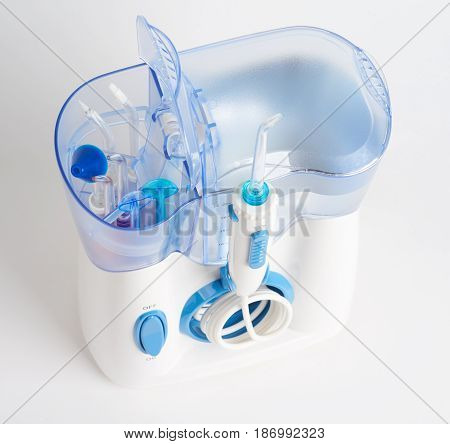 Oral irrigator for domestic usage with tips storage open on white background