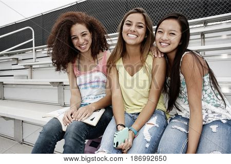 School friends sitting together on bleachers