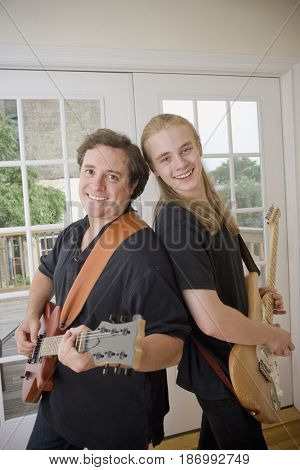 Caucasian father and son playing guitars