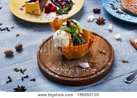 Ice cream served in waffle bowl. Three colored ice-cream scoops with mint, peanuts and chocolate sauce on wooden desk.