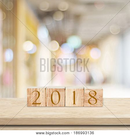 Wooden cubes with 2018 on table over blur bokeh background with copy space for text new year and christmas card backgroundtemplate