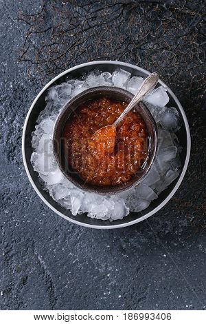 Bowl of red caviar on ice with spoon served over black stone texture background. Top view with space