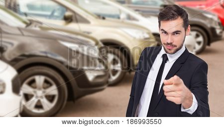 Digital composite of Businessman pointing against car in showroom