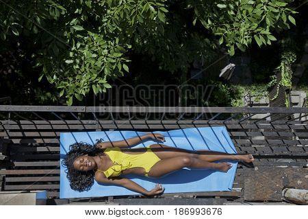 Black woman sunbathing on fire escape