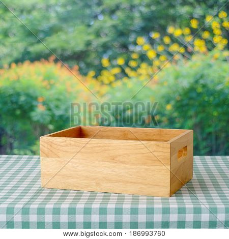 Empty wooden box on table with green scott pattern tablecloth over blur tree with bokeh light background product display montage