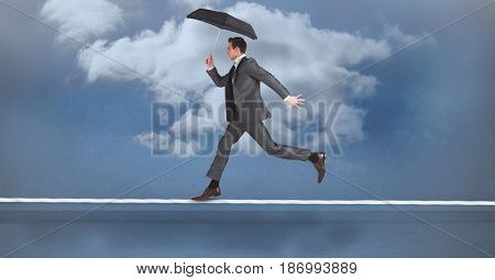 Digital composite of Businessman with umbrella running on rope against sky