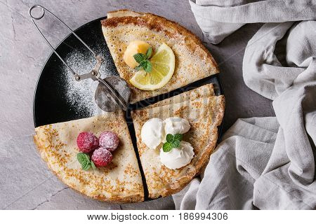 Sweet crepes pancakes with different fillings fresh raspberries, lemon curd, mascarpone cheese, mint, sugar powder with vintage sieve, textile linen over gray texture background. Top view with space