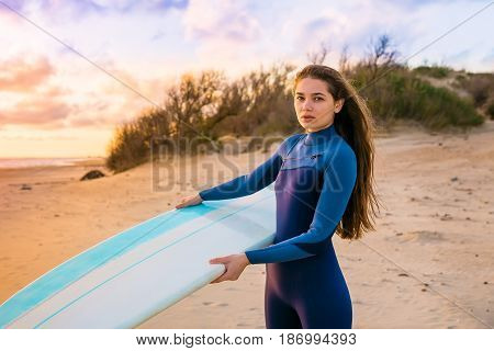 Beautiful surf girl with long hair holding surfboard on a beach at sunset or sunrise. Surfer and ocean