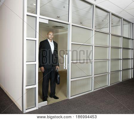 Mixed race businessman standing in office doorway