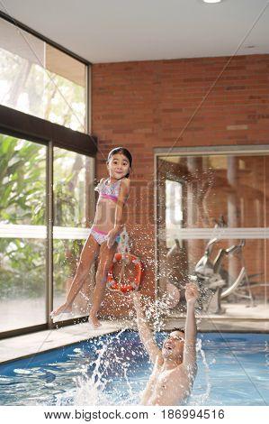 Hispanic father throwing daughter in swimming pool