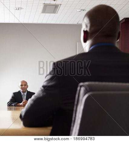 Mixed race businessmen having meeting in conference room