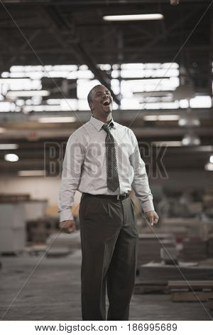 Black businessman laughing in warehouse