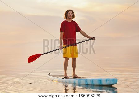 Caucasian man standing on paddle board