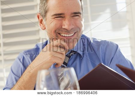 Smiling Caucasian businessman holding menu in restaurant