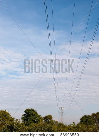Electric Wires On A Pylon In The Distance Spreading Across The Clear Blue And Cloudy Sky Beautiful C