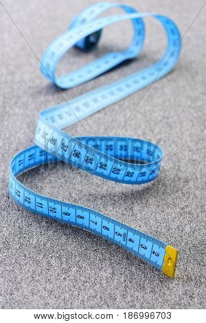 Concept of metering sewing and handicraft: blue measuring tape with black numbers and yellow end curling on light grey background selective focus