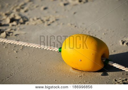 yellow buoy on the beach, safety zone for swimming, caution on the beach