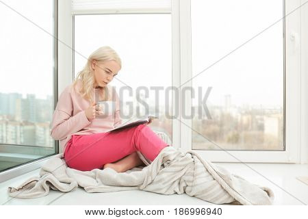 Beautiful young woman drinking coffee and reading book while sitting on windowsill at home