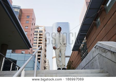 African American businessman standing at top of stairs