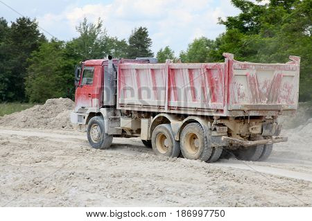 Dump truck Tatra work in quarry, red car