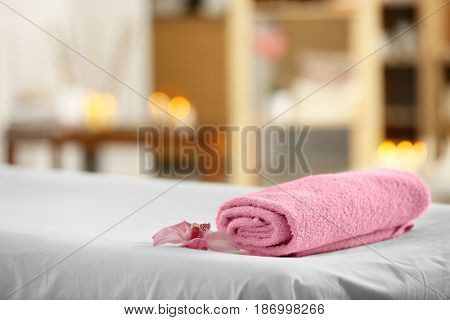 Towel and flower on massage table in modern spa salon