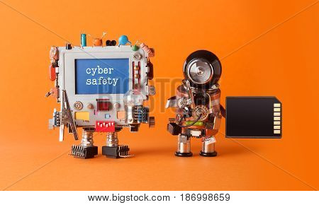 Cyber safety internet crime security concept. Alert message hacked computer. Robotic IT specialist memory card antivirus software. Orange background, shallow depth field.