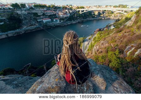 Girl with blonde dreadlocks sitting on a rock and looks at Douro river, Porto, Portugal.