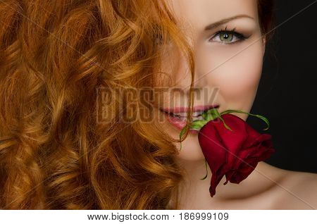 woman with red hair holds beautiful rose in her mouth