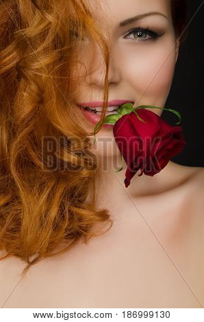 young woman with long red hair holds beautiful rose in her mouth