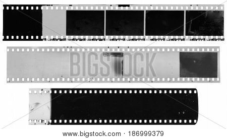 Old used dusty and scratched black and white celluloid film strips isolated on white background