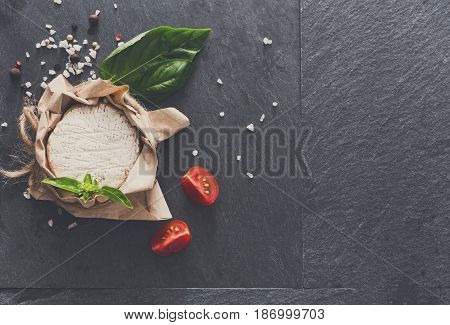 Brie or camembert cheese on black stone background, top view, filtered image