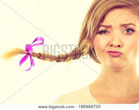 Face expression fooling around concept. Teenage girl in blonde braid windblown hair making funny silly faces.
