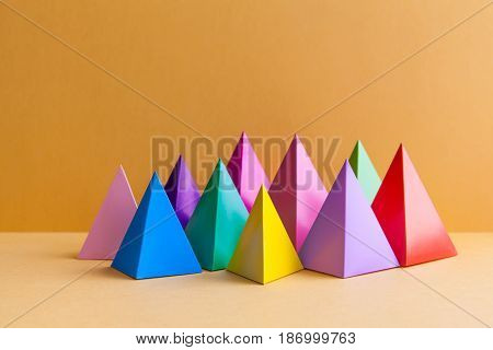 Colorful abstract geometric figures still life. Three-dimensional pyramid prism rectangular cube on orange background. Yellow blue pink green violet red colored objects.