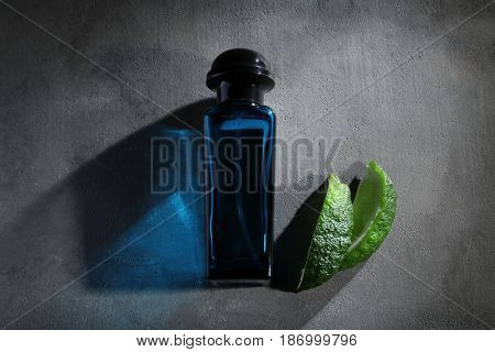Bottle of modern male perfume and lime slices on grey textured background