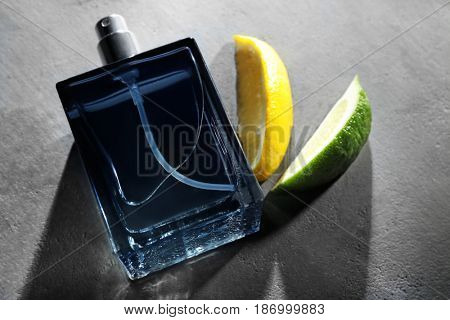 Bottle of modern male perfume and citrus slices on grey textured background