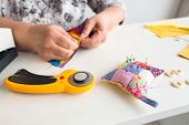 needlework and hand quilting - tailor hands sew multicolored patchwork fabric with the use of needles, cushions for pins, buttons and rotary fabric cutters on white background poster