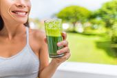 Green smoothie healthy lifestyle fitness woman drinking spinach juice cleanse in summer background at home. Happy fit girl living active life juicing. poster