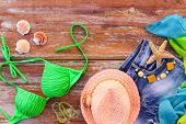 Summer women's clothing and accessories: hat, bathing suit, denim shorts, pareo, shells. Top view. poster